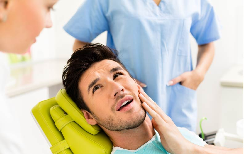 man at dentist holding mouth pain