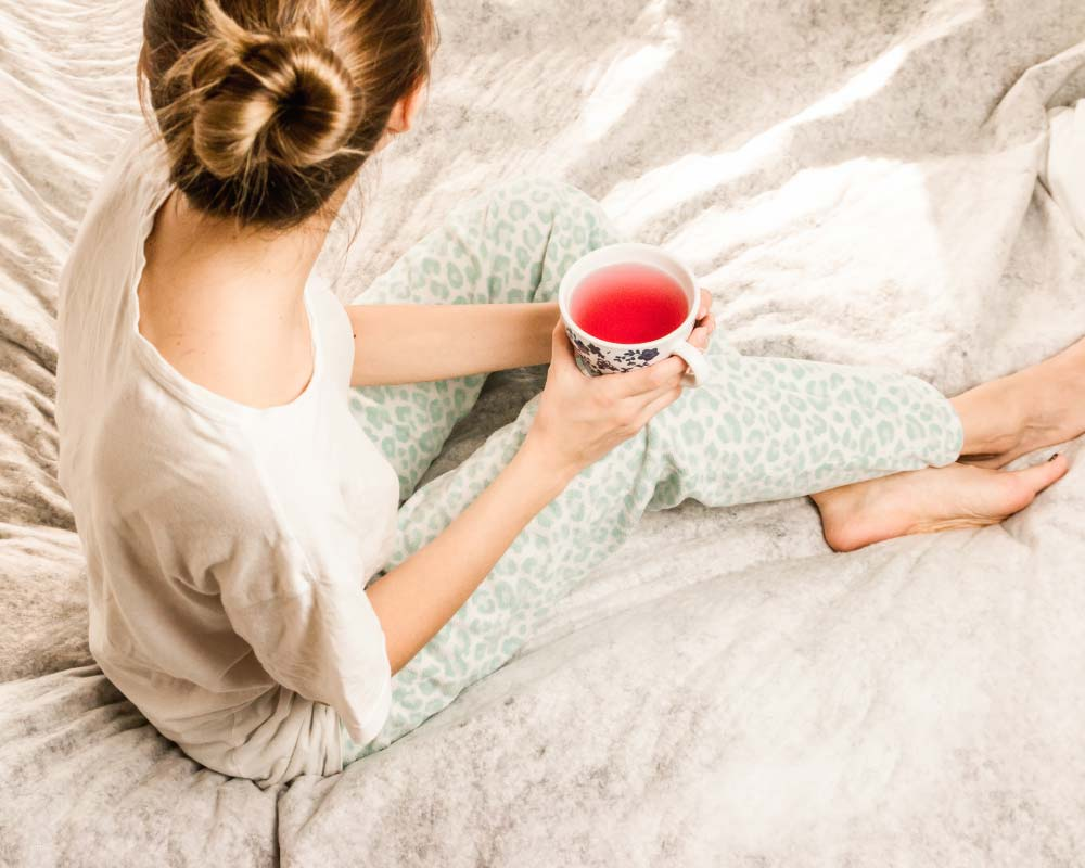 woman in bed drinking tea nightly routine