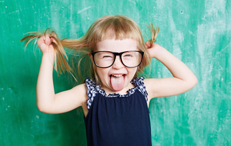 little blonde girl in pigtails and glasses pulling hair and sticking out tongue in front of chalkboard
