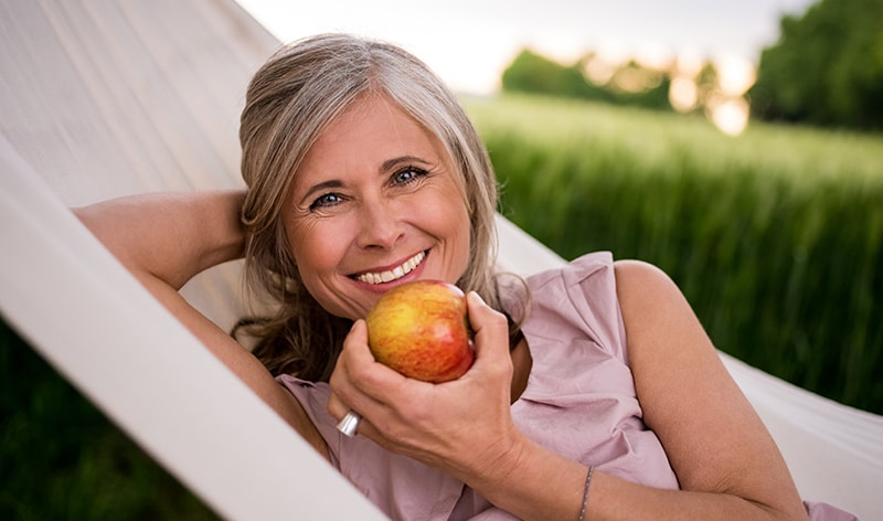 woman with sleeveless pink blouse, smiling, holding apple, and laying in hammock