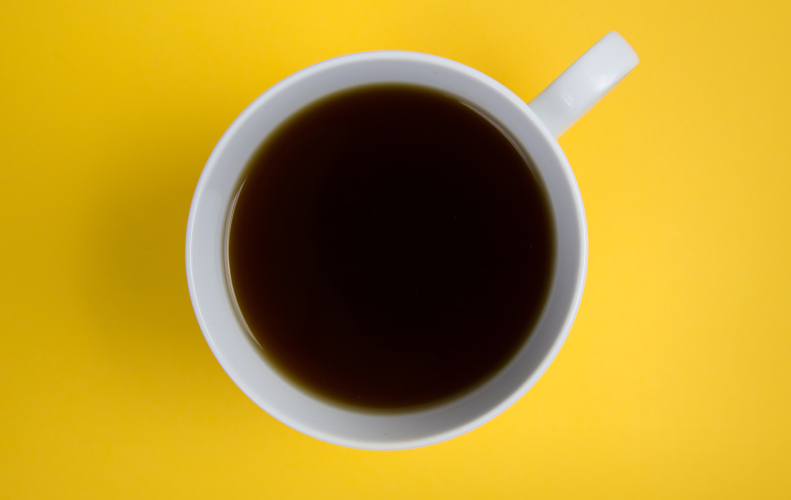 Aerial view of a white mug filled with brown coffee on a yellow counter