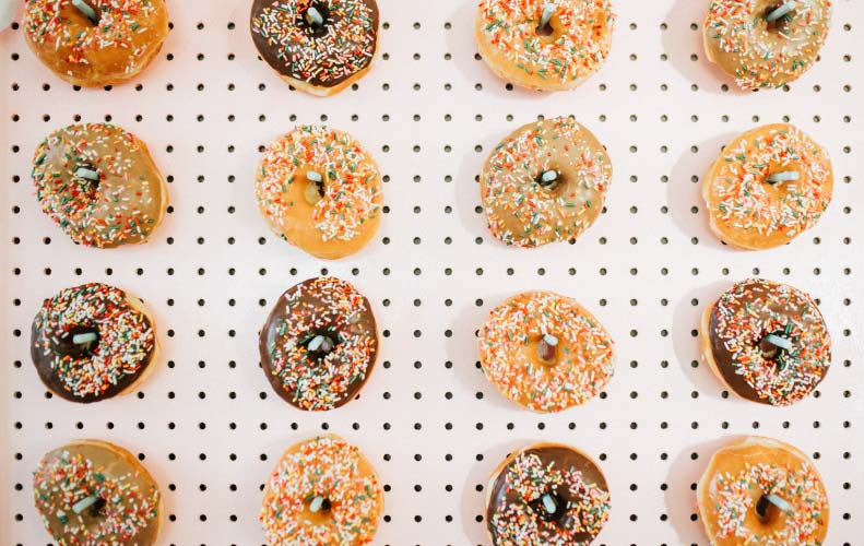 White pegboard filled with columns of chocolate and plain donuts covered with icing and sprinkles